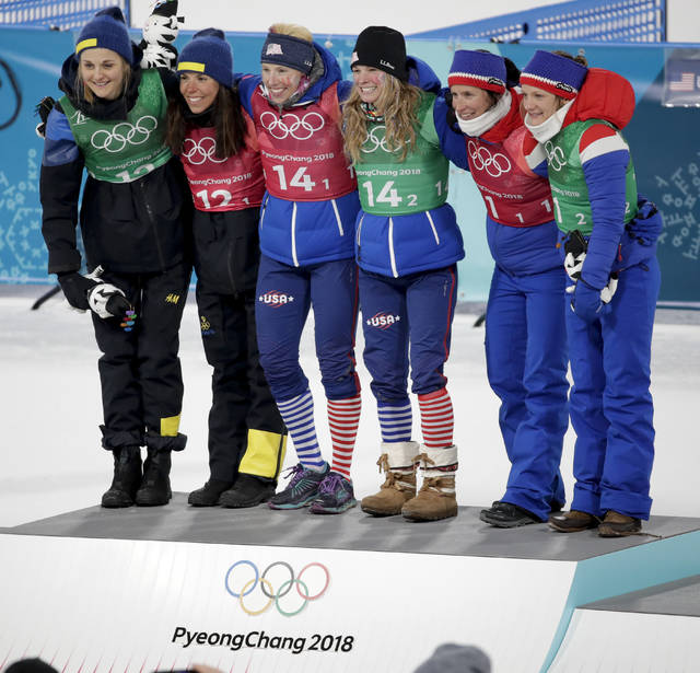 Gold medal winners Kikkan Randall, of the United States, and Jessica Diggins is flanked by silver medal winners Stina Nilsson, of Sweden, and Charlotte Kalla, left, and bronze medal winners Marit Bjoergen, of Norway, and Maiken Caspersen Falla during the venue ceremony after women's team sprint freestyle cross-country skiing final at the 2018 Winter Olympics in Pyeongchang, South Korea, Wednesday, Feb. 21, 2018. (AP Photo/Dmitri Lovetsky)