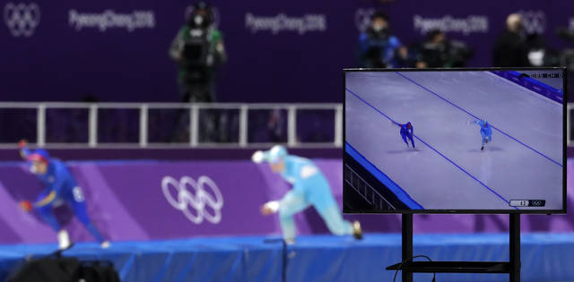 FILE- In this Feb. 19, 2018, photo, a TV screen shows Pedro Causil of Colombia, left on TV and rear left, and Stanislav Palkin of Kazakhstan, right on TV and rear center, competing during the men's 500 meters speedskating race at the Gangneung Oval at the 2018 Winter Olympics in Gangneung, South Korea. When it comes to the Olympics, too much choice can paralyze you with indecision. (AP Photo/Petr David Josek, File)