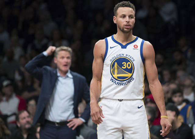"""FILE - In this Nov. 19, 2017, file photo, Golden State Warriors guard Stephen Curry stands on the court as coach Steve Kerr gestures during the second half of the team's NBA basketball game against the Brooklyn Nets in New York. At 44-14 and loaded with four All-Stars, the Warriors are still very good, but not as good they've been. """"This year we've had a pretty solid season, but feel that we can play a lot better,"""" Curry said. """"So that's what we're trying to do this next 20 games before another championship run."""" (AP Photo/Mary Altaffer, File)"""