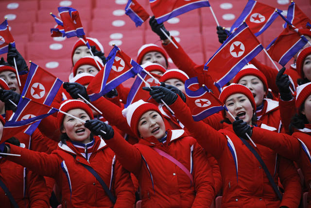 FILE - In this Feb. 14, 2018, file photo, members of the North Korean delegation wave flags at the women's slalom at Yongpyong alpine center at the 2018 Winter Olympics in Pyeongchang, South Korea. While in South Korea, the North Koreans wear the same uniforms, move together whenever possible and operate as a tightly knit team. (AP Photo/Christophe Ena, File)