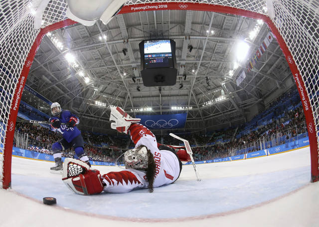 Jocelyne Lamoureux-Davidson (17), of the United States, scores a game winning goal against goalie Shannon Szabados (1), of Canada, in the penalty shootout during the women's gold medal hockey game at the 2018 Winter Olympics in Gangneung, South Korea, Thursday, Feb. 22, 2018. (Bruce Bennett/Pool Photo via AP)