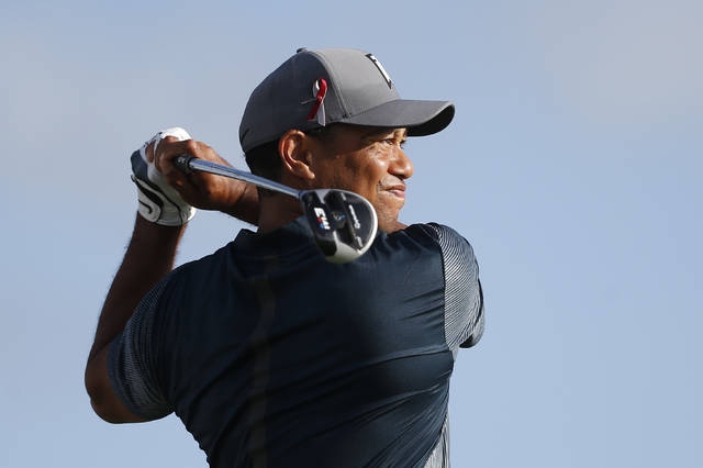Tiger Woods tees off on the 13th tee during the first round of the Honda Classic golf tournament, Thursday, Feb. 22, 2018, in Palm Beach Gardens, Fla. Golfers wore a ribbon on their caps in memory of the students and faculty killed in the Marjory Stoneman Douglas High School shooting. (AP Photo/Wilfredo Lee)