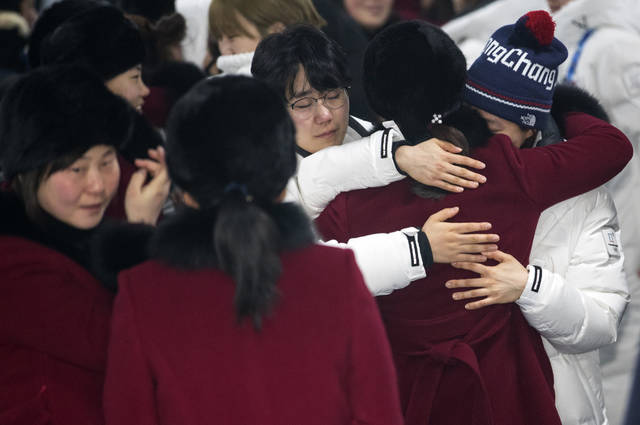 A North Korean women's hockey team player hugs her South Korean teammates, wearing white coats, before returning to North Korea, at Olympic Village in Gangneung, South Korea, Monday, Feb. 26, 2018. (Yun Dong-jin/Yonhap via AP)