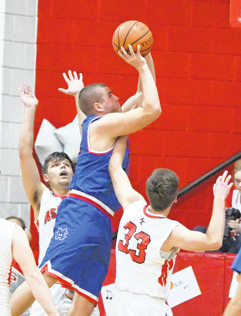 Trey Uetrecht goes up against a pair of defenders, Alex Pence and Logan Kelly, during Tuesday's boys basketball game at East Clinton High School.