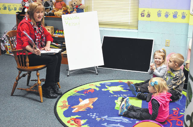"Priscilla Clark reads Lisa Wheeler's ""Dino Football"" to, from left, Kelsey Johnson, Wesley Huetskamp and McKinley Hartsell during the Wilmington Public Library's story time on Thursday. Each week story time has a different theme, and this week it's ""Super Bowl/Sports."" The library hosts story times for preschool children and babies at the Main Library and at the Clinton-Massie Branch. At the Main Library: Wednesdays 10 a.m. — Babies & Toddlers (Birth - 3 years); Wednesdays 11 a.m. — Pre-K (3 years - kindergarten); and Thursdays 11 a.m. — All ages; and at the Clinton-Massie Branch: Tuesdays at 11 a.m. for all ages. John Hamilton 