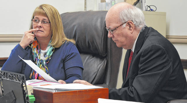 From left, Clinton County Commissioner Brenda K. Woods and Clinton County Commissioners President Patrick Haley mull the terms and language of a loan agreement Wednesday with the Murphy Theatre nonprofit corporation.