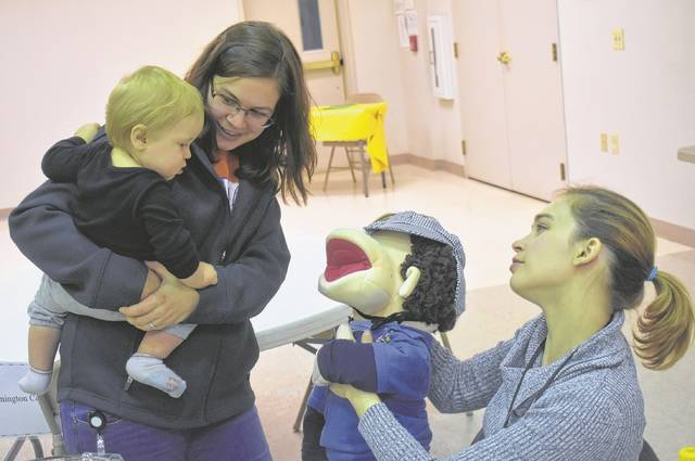 """Brody Jenkins and teacher Brittanie Bartlett, left, meet Tiesha Widmer and Wally the puppet during the Clinton County Community Action Head Start's Community Night at the Wilmington Presbyterian Church on Thursday. Widmer is a licensed Early Childhood Mental Health Prevention Specialist at Solutions CCRC in Wilmington. Wally is one of several puppets used in a social-emotional curriculum called Incredible Years """"Dina School."""""""