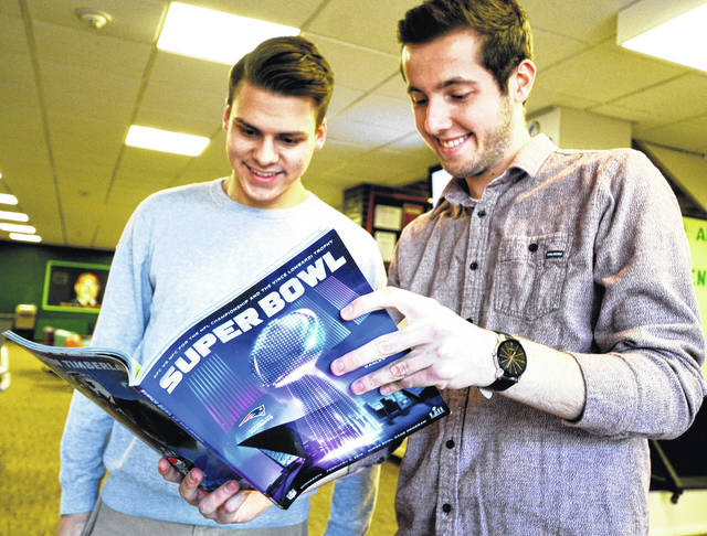 Freshmen Abram Werle (left) and Jacob Franke view Wilmington College's ad in an advance copy of the Super Bowl program.