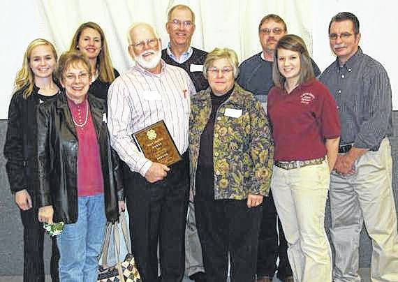 """In 2010, Gary Quallen, in the foreground holding a plaque, was awarded the """"Clinton County Friend of 4-H""""."""