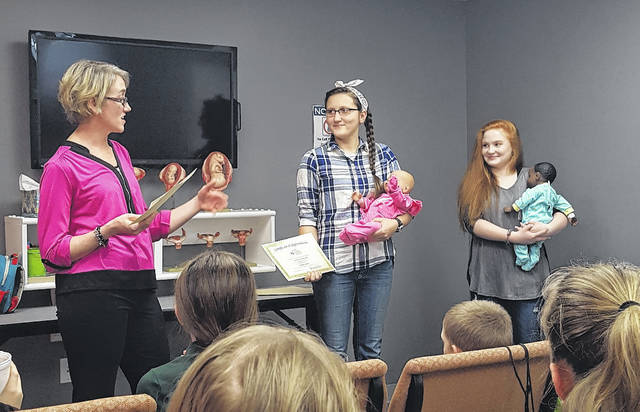 """From left, New Life Clinic Director Sherry Weller presents certificates to Courtney Kirkendall, who named a Real-Care doll """"Mindy Eileen"""" in honor of her great aunt, and Abigail Proffitt, who named a doll """"Mary Lou"""" in honor of her late grandmother."""