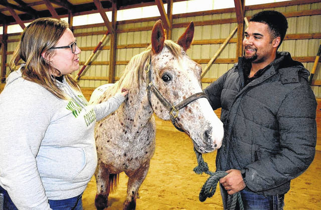 """Katie Finkes-Turner, equestrian team coach, and sophomore team members Michael Porter discuss """"barn favorite"""" Speckles, who is one of the College's horses that will be randomly selected for the two home equitation shows this month at WC's Equine Center."""