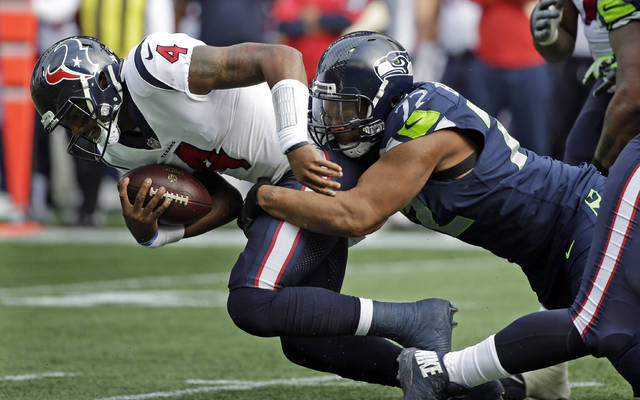 FILE - In this Oct. 29, 2017, file photo, Houston Texans quarterback Deshaun Watson (4) is sacked by Seattle Seahawks defensive end Michael Bennett in the first half of an NFL football game in Seattle. The Super Bowl champion Philadelphia Eagles have acquired three-time Pro Bowl defensive end Michael Bennett from the Seattle Seahawks, two people familiar with the trade told The Associated Press Wednesday, March 7, 2018. (AP Photo/Elaine Thompson, File)