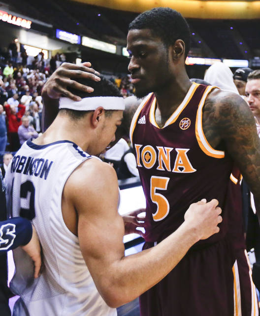 FILE - In this March 7, 2016, file photo, Iona guard A.J. English (5) embraces Monmouth guard Justin Robinson (12) after Iona's 79-76 win in an NCAA college basketball game for the championship of the Metro Atlantic Athletic Conference men's tournament in Albany, N.Y. Monmouth earned national recognition that season by beating UCLA and Notre Dame, but the Hawks lost in the conference tournament and went to the NIT. (AP Photo/Mike Groll, File)