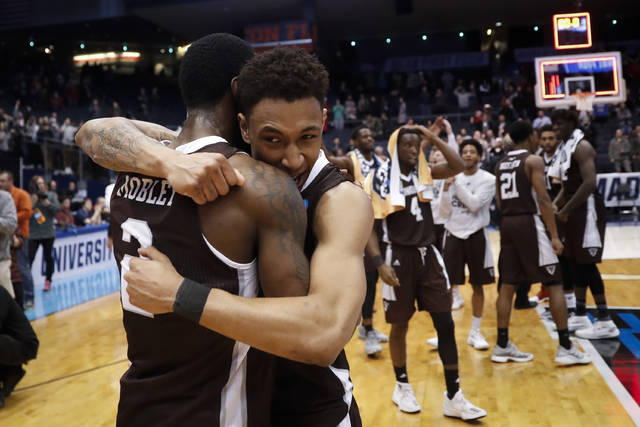 St. Bonaventure's Jaylen Adams, center, hugs Matt Mobley (2) after their First Four game of the NCAA men's college basketball tournament against UCLA, Tuesday, March 13, 2018, in Dayton, Ohio. St. Bonaventure won 65-58. (AP Photo/John Minchillo)
