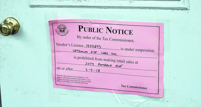 This sign from the state was posted on the front door of Optimum Eyecare on Friday.
