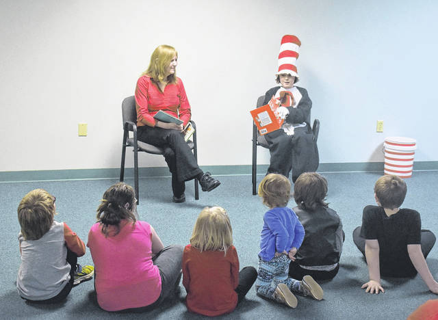 """MacKenzie Pyle dressed as the Cat in the Hat reads """"Green Eggs and Ham"""" to guests at Wilmington Public Library's Dr. Seuss Birthday Party on Thursday."""