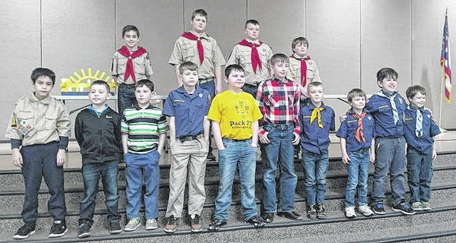 Scouts receive awards at the Blue and Gold banquet with the four new Boy Scouts in the back row.