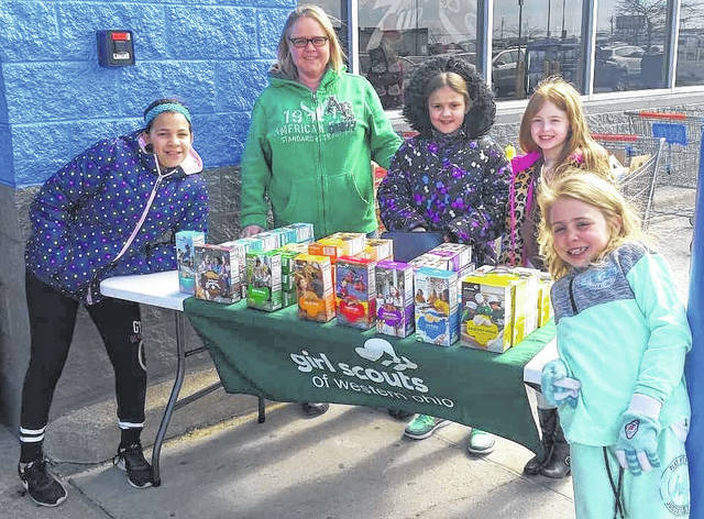 The cheerful members of Girl Scout Troop 34488 raise funds selling cookies Sunday afternoon at Wal-Mart in Wilmington. Along with Scout Mom Wendy Nelson are, from left, Nevaeh Nance, Annika Nelson, Kelsey Schanda and Kyanna Hagen.