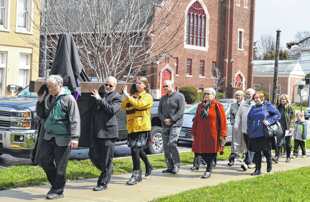 In observance of Good Friday, a shrouded cross is carried through a portion of downtown Wilmington in conjunction with a community service held by the Wilmington Area Ministerial Association (WAMA). Beforehand at the First Christian Church (Disciples of Christ), seven clergy read scripture followed by comments of reflection: Rev. June Fryman, Rev. Dan Mayo, Rev. Debbie Linville, Chaplain Veronica Grabill, Pastor Dave Hinman, Father Mike Holloran, Rev. Marie Smith and Pastor Nancy McCormick. For more photos, please visit www.wnewsj.com .