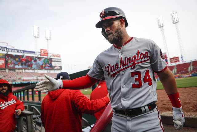 Washington Nationals' Bryce Harper celebrates in the dugout after hitting a solo home run off Cincinnati Reds starting pitcher Sal Romano in the sixth inning of a baseball game, Sunday, April 1, 2018, in Cincinnati. (AP Photo/John Minchillo)