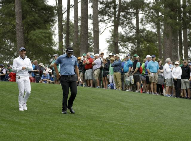 Jon Rahm, of Spain, and Rory McIlroy, of Northern Ireland, walk on the fourth hole during a practice round for the Masters golf tournament Wednesday, April 4, 2018, in Augusta, Ga. (AP Photo/Matt Slocum)