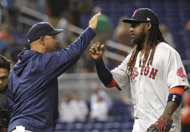 Boston Red Sox manager Alex Cora, left, high-fives Hanley Ramirez after a baseball game against the Miami Marlins, Tuesday, April 3, 2018, in Miami. The Red Sox defeated the Marlins 4-2 in thirteen innings. (AP Photo/Lynne Sladky)