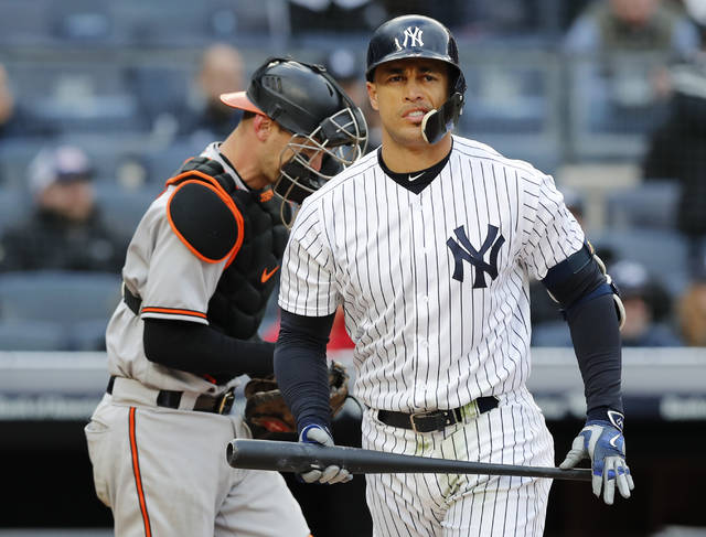 New York Yankees' Giancarlo Stanton reacts after he stuck out stranding two runners for the final out during the 12th inning of a baseball game in New York, Sunday, April 8, 2018. The Orioles defeated the Yankees 8-7. Orioles catcher Caleb Joseph is at left. (AP Photo/Kathy Willens)