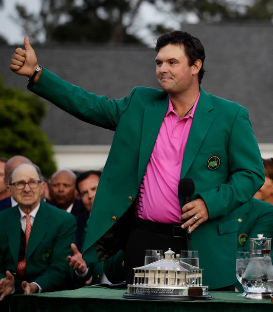 Patrick Reed gives a thumbs up after being presented with the championship trophy after winning the Masters golf tournament Sunday, April 8, 2018, in Augusta, Ga. (AP Photo/Chris Carlson)
