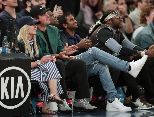 Masters golf tournament champion Patrick Reed, second from left, and is wife, Justine Karain, left watch play between the New York Knicks and the Cleveland Cavaliers during an NBA basketball game, Monday, April 9, 2018, in New York. (AP Photo/Julie Jacobson)