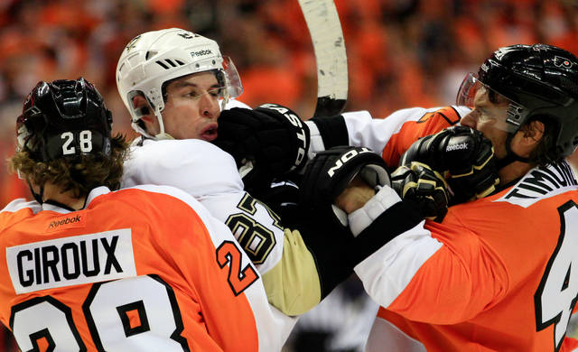 """FILE - In this April 15, 2012, file photo, Philadelphia Flyers Claude Giroux, left, holds on to Pittsburgh Penguins' Sidney Crosby as Kimmo Timonen, right, lands a punch to Crosby's jaw during the first period of Game 3 in a first-round NHL Stanley Cup playoffs hockey series in Philadelphia. The NHL's divisional playoff format was brought back specifically to ignite old and create new rivalries, which has been a successful venture even if hate looks different than it did in the days of the """"Broad Street Bullies."""" Playoff rivalries are no longer about dropping the gloves or even laying out bone-crushing hits like in past eras. (AP Photo/Tom Mihalek, File)"""