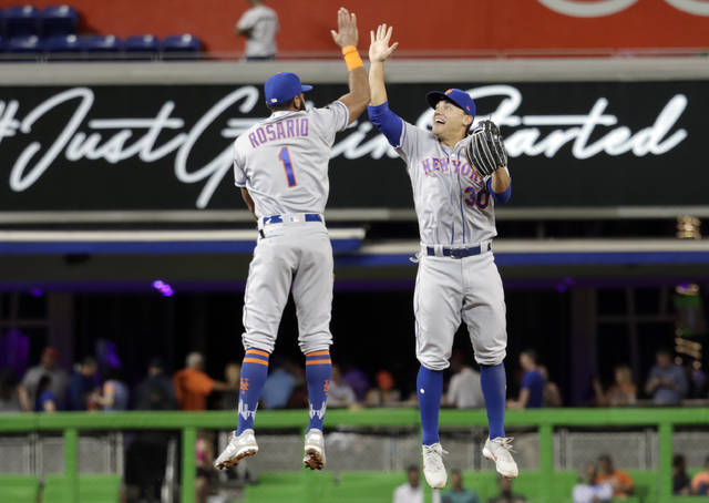 New York Mets' Amed Rosario (1) and Michael Conforto (30) celebrate after the Mets defeated the Marlins 4-1 during a baseball game, Wednesday, April 11, 2018, in Miami. (AP Photo/Lynne Sladky)