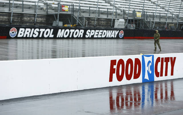 A person walks along the track in the rain before a NASCAR Cup Series auto race, Sunday, April 15, 2018, in Bristol, Tenn. (AP Photo/Wade Payne)