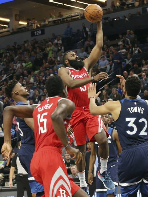 Houston Rockets' James Harden, center, shoots as Minnesota Timberwolves' Jimmy Butler, left, and Karl-Anthony Towns, right, during the second half of Game 4 in an NBA basketball first-round playoff series Monday, April 23, 2018, in Minneapolis. The Rockets won 119-100. Harden led the Rockets with 36 points. (AP Photo/Jim Mone)