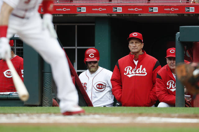 Cincinnati Reds interim manager Jim Riggleman, center right, works in the dugout during the first inning of a baseball game against the Atlanta Braves, Monday, April 23, 2018, in Cincinnati. (AP Photo/John Minchillo)