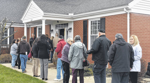 Clients of Optimum Eyecare stand in line outside the facility Tuesday to get access to their records.