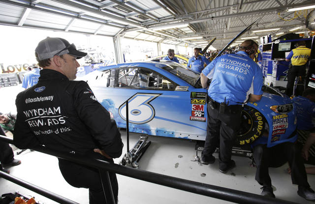 Driver Matt Kenseth stands in the garage following a failed car inspection during a practice round for this weekend's NASCAR Cup Series auto race at Kansas Speedway Friday, May 11, 2018, in Kansas City, Kan. (AP Photo/Colin E. Braley)