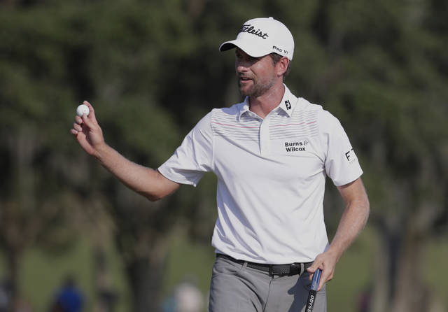 Webb Simpson holds up his ball on the 18th green during the second round of The Players Championship golf tournament Friday, May 11, 2018, in Ponte Vedra Beach, Fla. (AP Photo/Lynne Sladky)