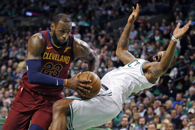 Cleveland Cavaliers forward LeBron James (23) drives against the defense of Boston Celtics forward Marcus Morris during the first quarter of Game 1 of the NBA basketball Eastern Conference Finals, Sunday, May 13, 2018, in Boston. (AP Photo/Michael Dwyer)