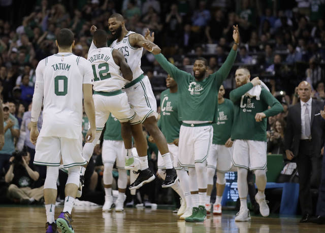 Boston Celtics guard Terry Rozier (12) and forward Marcus Morris leap in celebration near the end of Game 2 of the team's NBA basketball Eastern Conference finals against the Cleveland Cavaliers, Tuesday, May 15, 2018, in Boston. (AP Photo/Charles Krupa)