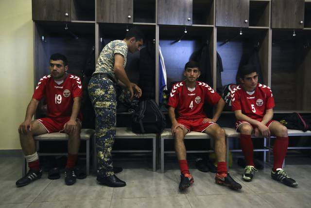 In this Friday, May 11, 2018 photo, an army officer prepares for training as his teammates listen to the coach of the soccer national team of the self-proclaimed Republic of Artsakh, in Stepanakert, the capital of the disputed territory of Nagorno-Karabakh. The ethnic Armenian team has the shirts and the shoes, and even practices five days each week on an artificial field a short distance from the center of Stepanakert. The reason for the lack of opponents has nothing to do with sports and everything to do with politics. UEFA and FIFA have a general policy of not allowing teams into competition if they don't represent an internationally recognized country or territory. (AP Photo/Thanassis Stavrakis)