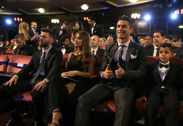FILE - In this Monday, Oct. 23, 2017 file photo, Portuguese soccer player Christiano Ronaldo, second from right, and son Cristiano Ronaldo Jr., right, sit beside Argentinian soccer player Lionel Messi, left, and wife Antonella during the The Best FIFA 2017 Awards at the Palladium Theatre in London. Cristiano Ronaldo and Lionel Messi put up impressive numbers, in life and on the field, going into a fourth World Cup for each. So much has happened for football's standout stars since the 2014 tournament left both still lacking the game's most coveted prize. (AP Photo/Alastair Grant, File)