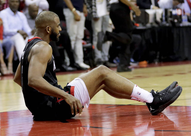 Houston Rockets guard Chris Paul sits on the floor after being hurt during the second half in Game 5 against the Golden State Warriors in the NBA basketball playoffs Western Conference finals in Houston, Thursday, May 24, 2018. (AP Photo/David J. Phillip)
