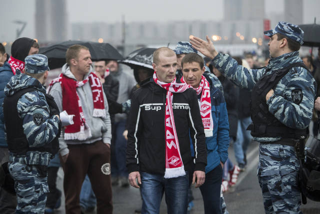 In this photo taken on Wednesday, April 18, 2018, police officers stop to check Spartak Moscow's supporters before the a Russian Premier League Championship soccer match between Spartak Moscow and Tosno in Moscow, Russia. Ahead of the World Cup, Russian authorities are cracking down on the hooligan culture in football. Groups which wreaked havoc two years ago report surveillance and threats from law enforcement. (AP Photo/Pavel Golovkin)