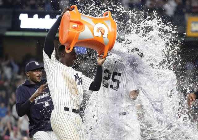 New York Yankees' Didi Gregorius dumps water onto Gleyber Torres (25) after Torres drove in the winning run during the 10th inning of the team's baseball game against the Houston Astros on Tuesday, May 29, 2018, in New York. The Yankees won 6-5. (AP Photo/Frank Franklin II)
