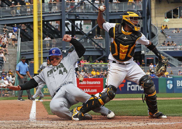 In this Monday, May 28, 2018 photo, Pittsburgh Pirates catcher Elias Diaz throws to first after getting the force out at home plate as Chicago Cubs' Anthony Rizzo slides in hard during the eighth inning of a baseball game in Pittsburgh. Diaz's errant throw to first allowed two runs to score. (AP Photo/Gene J. Puskar)