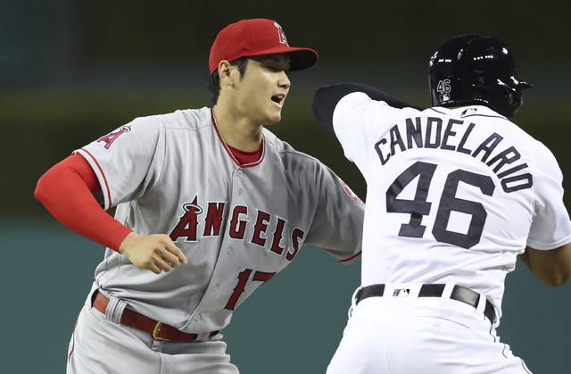 Los Angeles Angels starting pitcher Shohei Ohtani tags Detroit Tigers' Jeimer Candelario after Candelario grounded out to the pitcher during the fifth inning of a baseball game Wednesday, May 30, 2018, in Detroit. (AP Photo/Carlos Osorio)