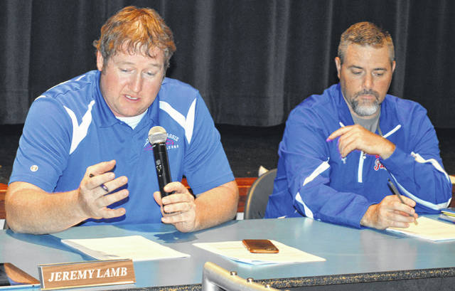 From left, Clinton-Massie Board of Education President Jeremy Lamb and board member Mike Goodall review a list of proposed cuts that was compiled after an earnings tax issue was defeated at the ballot box earlier this month.