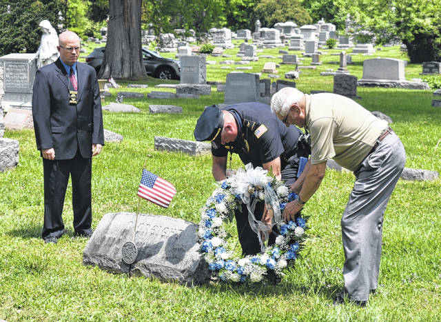 From left, WPD Chief Detective Josh Riley, WPD Police Chief Duane Weyand, and former WPD officer Franklin Copeland lay a memorial wreath at the tombstone of Ptl. Emery McCreight on Tuesday at Sugar Grove Cemetery in observation of National Peace Officers Memorial Day. McCreight was killed in the line of duty in 1922 while responding to a reported break-in at a store.
