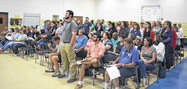Blanchester School District educators stand and listen as teacher and BEA Michelle Elston speaks to the school board at Monday's meeting.