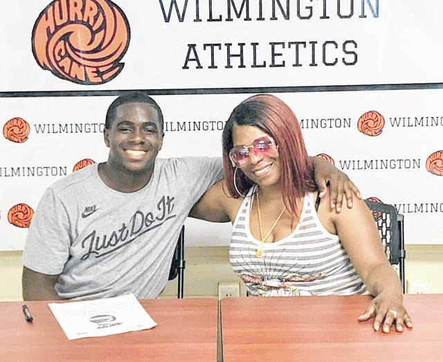 Wilmington High School senior Frantz Cherisca will continue his education and athletic career at Thomas More. Cherisca plans to play football for the Saints. In the photo, Cherisca is shown with his mother Rona Harris.